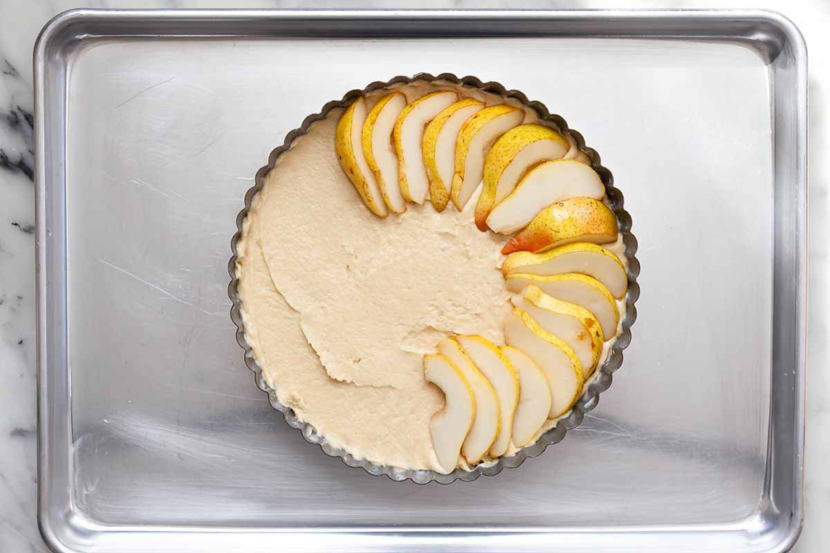 Easy Pear cake batter in a fluted tart tin with sliced pears partially arranged on top