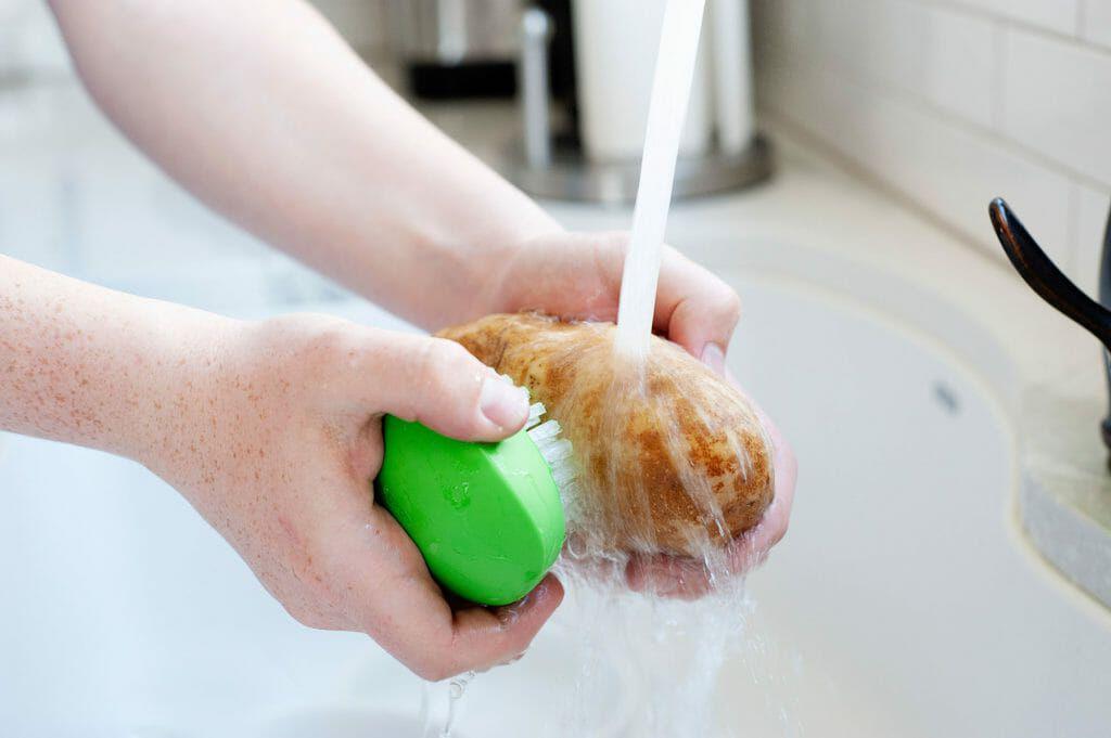 A russett potato being scrubbed under running water.