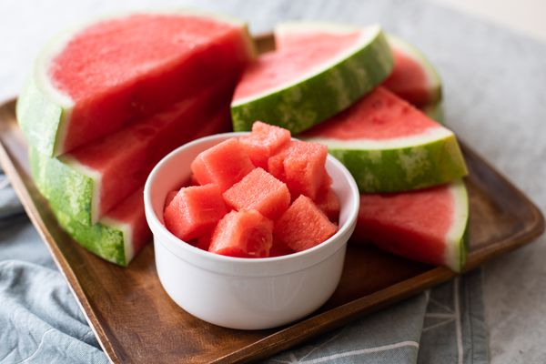 Bowl of watermelon cubes with watermelon slices behind it on a wood serving platter