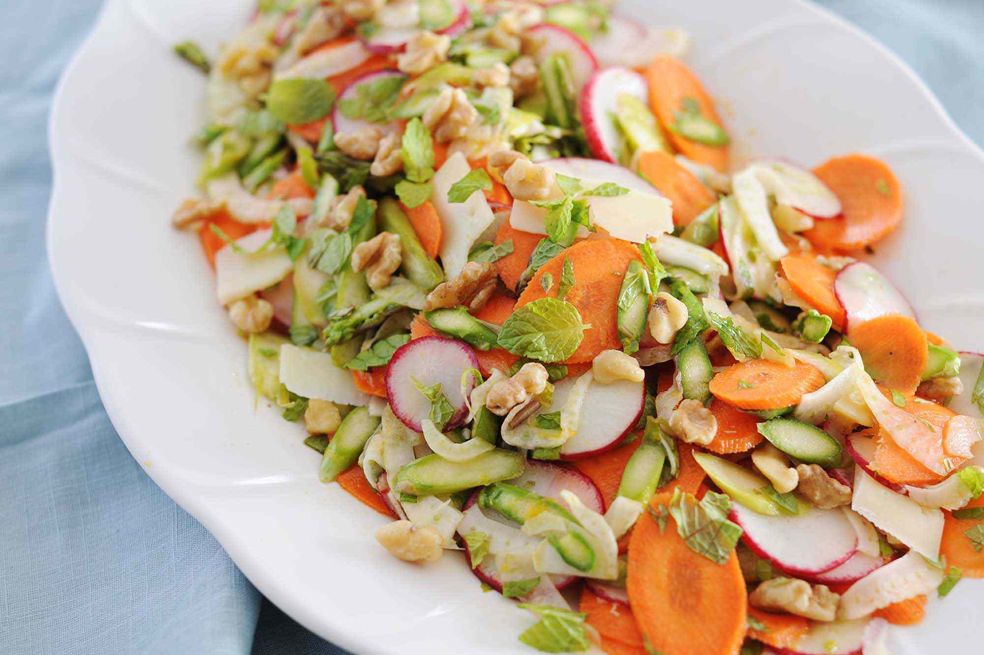 A white platter with an easy spring salad. Thinly sliced carrot, radish, fennel and asparagus are mixed together and mint leaves and chopped nuts are scattered around the top. The platter is on a light blue linen.