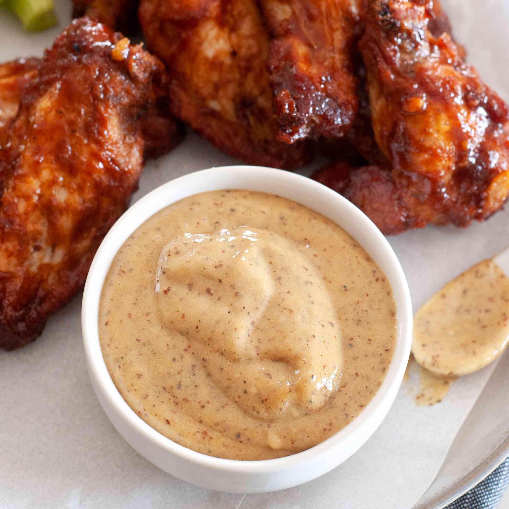 Homemade honey mustard served on a platter of chicken wings.