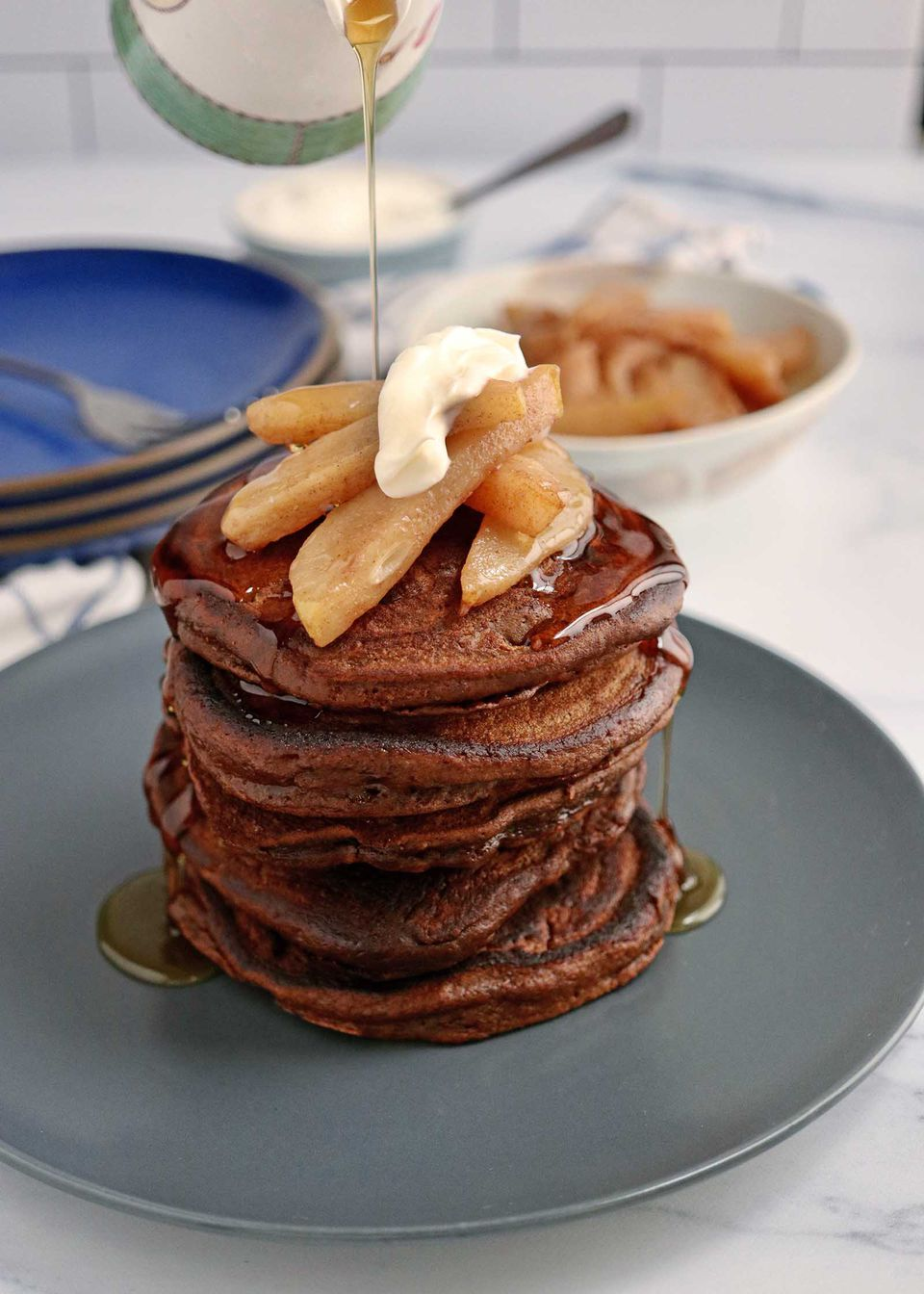 A stack of holiday pancakes topped with sliced pears and creme fraiche with syrup being poured over top.