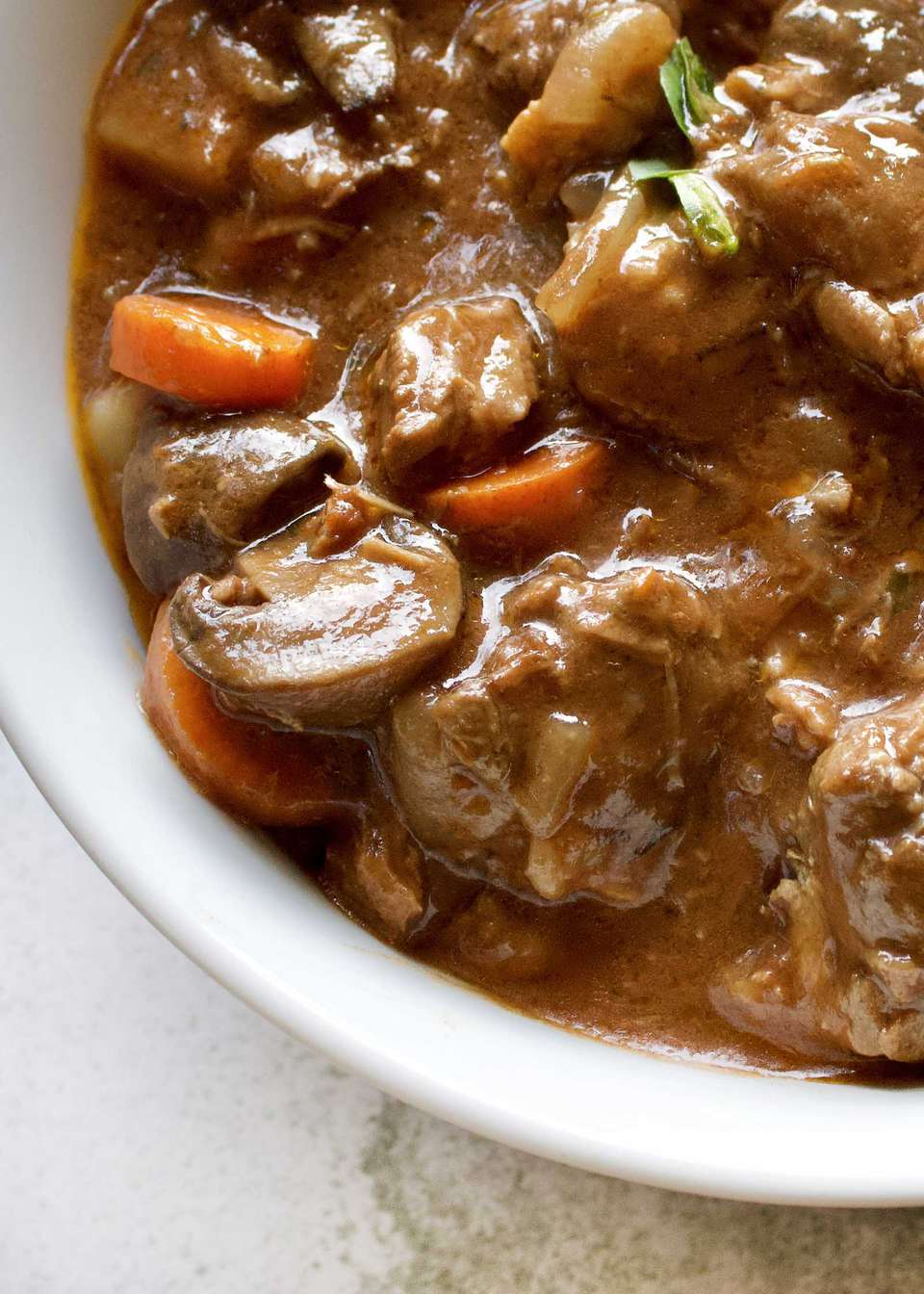 A thick bowl of Slow Cooker Beef Stew with chunks of meat, carrots and mushrooms visible.
