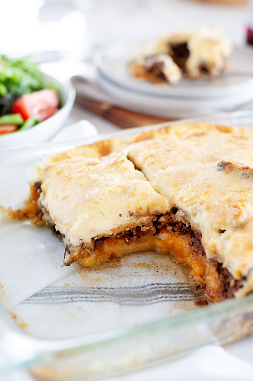 Sliced greek moussaka in a glass baking dish with a piece removed.