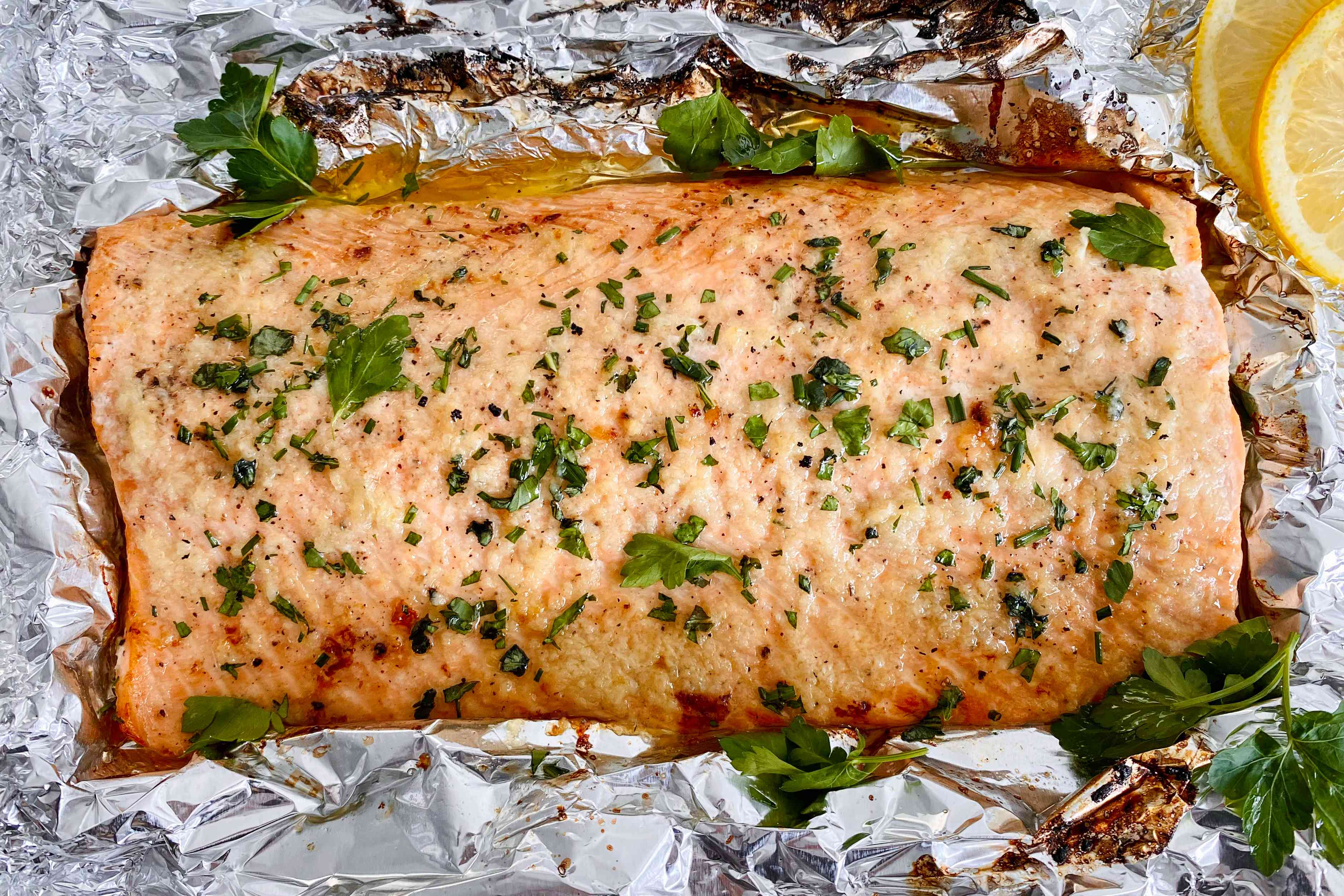 Garlic Butter Roasted Salmon topped with herbs and set on foil.