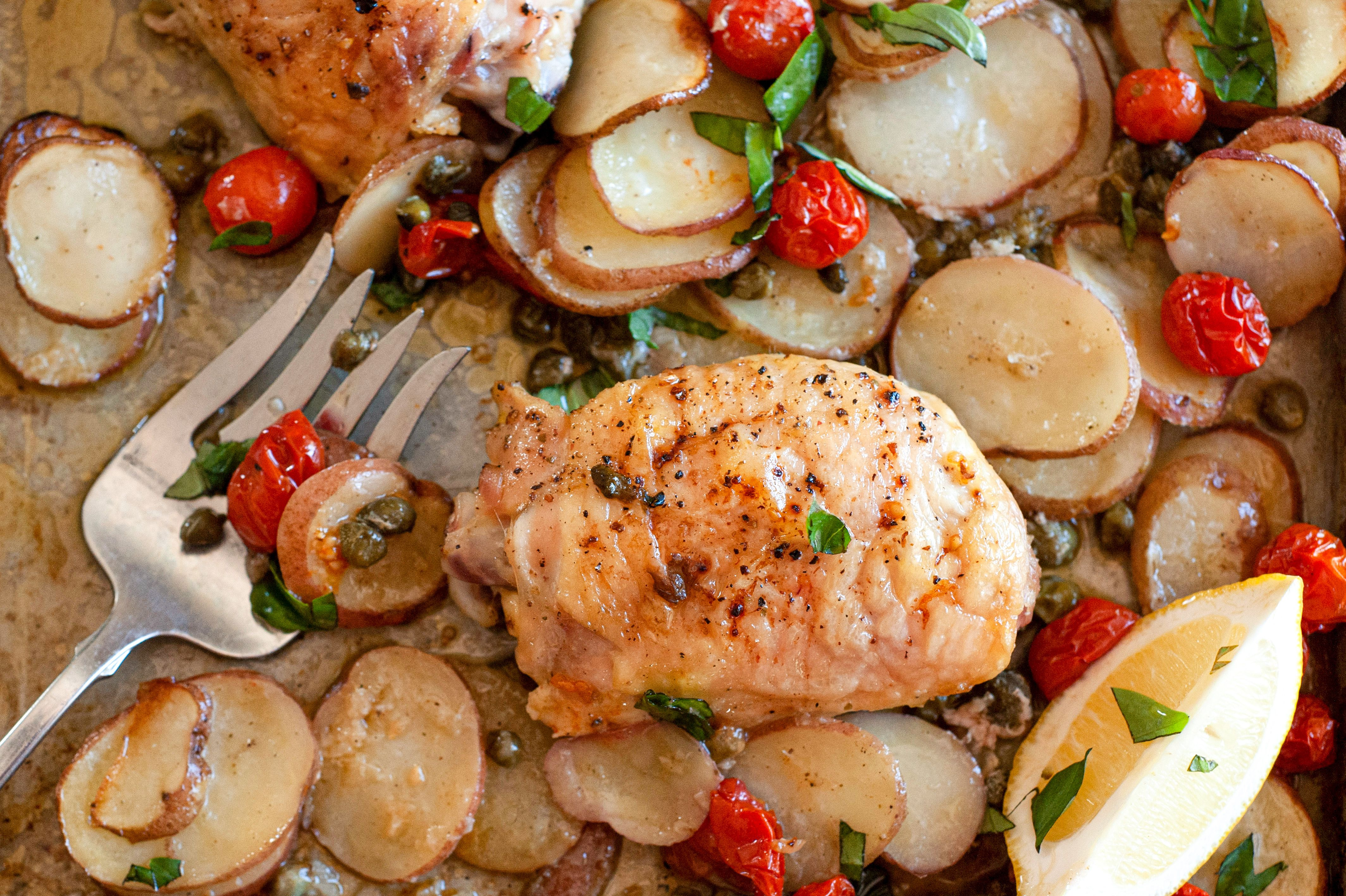 Sheet pan lemon chicken thighs with potatoes and veggies with a fork next to it on the pan.