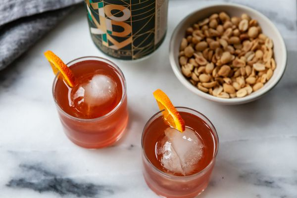 Overhead view of two Negronis with non alcoholic gin, bar nuts and an orange wedge.
