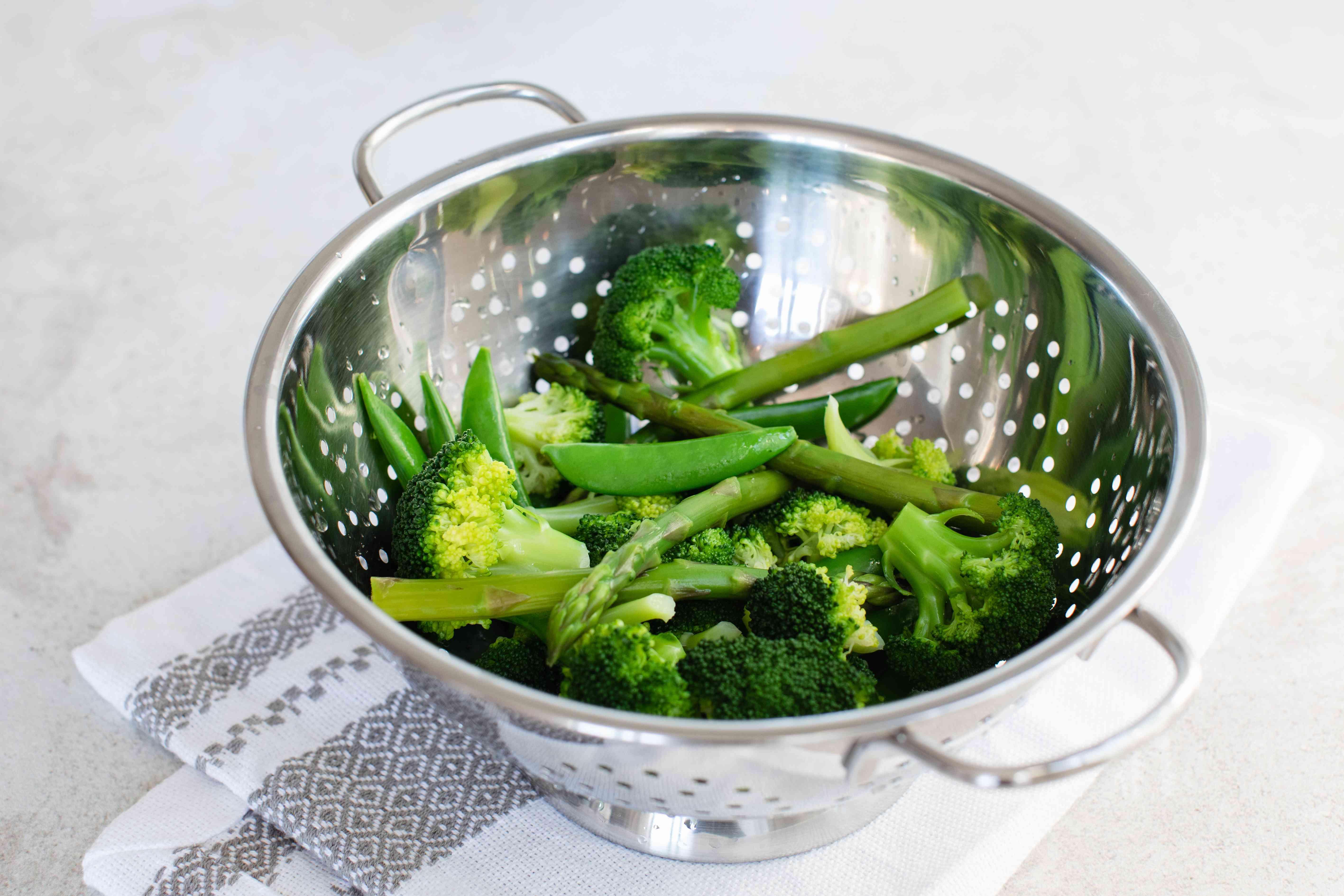Blanched broccoli in a strainer for a pasta primavera recipe.