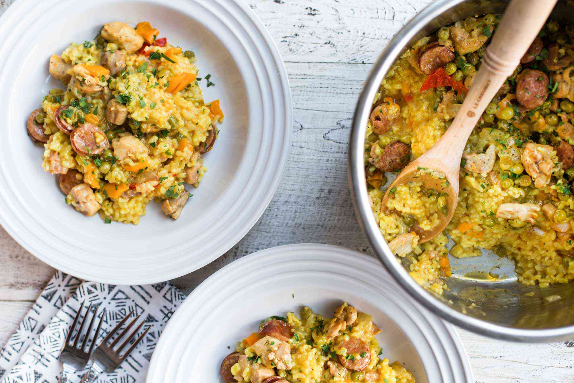 pressure cooker paella in the instant pot with two plates of paella alongsid