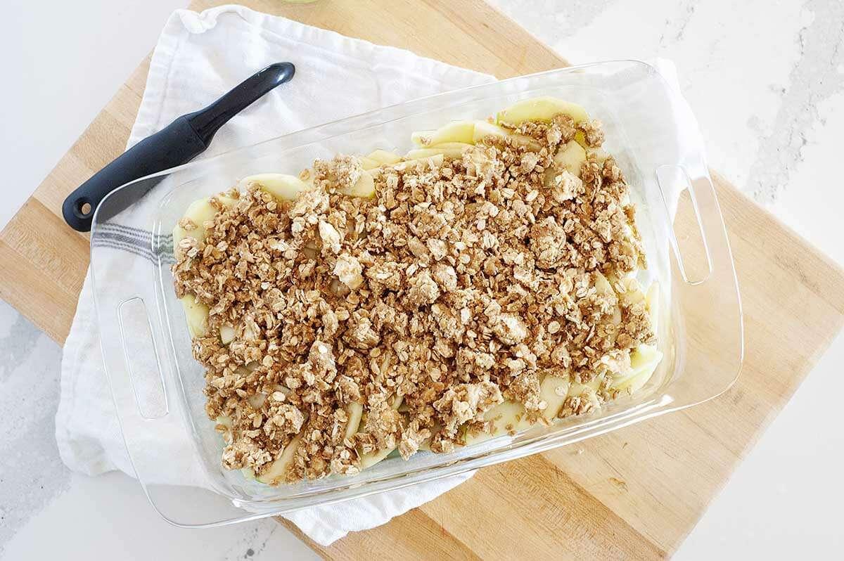Sliced apples topped with apple crisp topping for the best apple crisp.