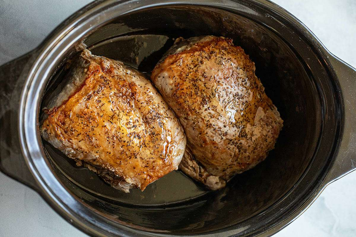 Two pork loins are set next to each other in a crock pot to show how to make slow cooker pork loin.