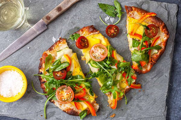How to Make Vegetable Pizza - flatbread pizza piled high with vegetables. Cut into slices on a parchment paper with a wooden handled knife nearby