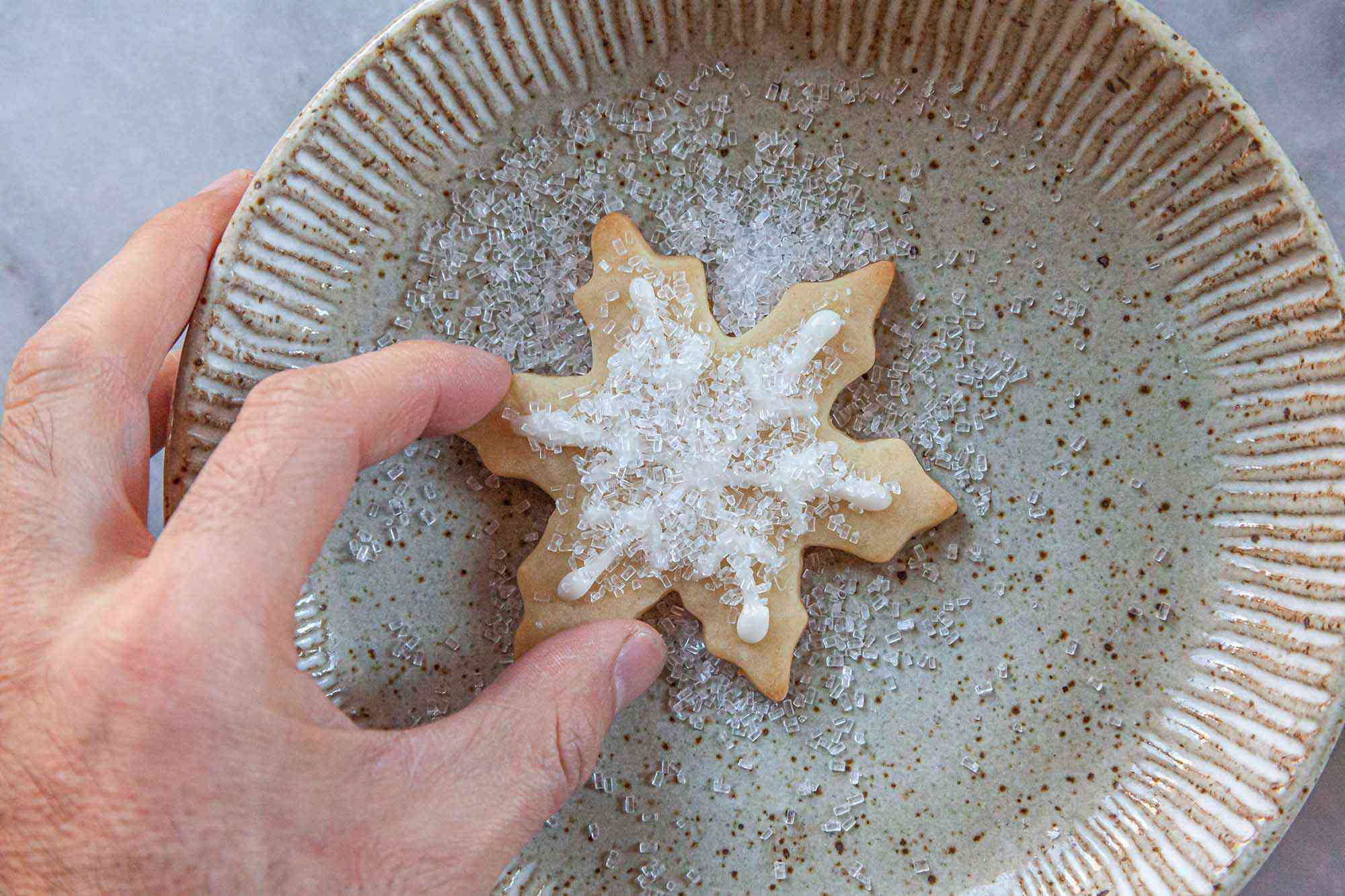 Sparkling sugar added to a snowflake sugar cookie decorated with Royal icing for sugar cookies.