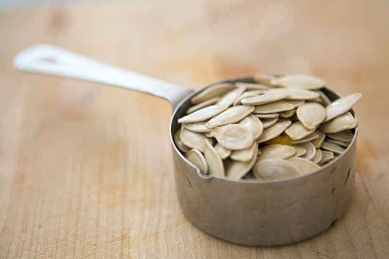 pumpkin seeds in measuring cup