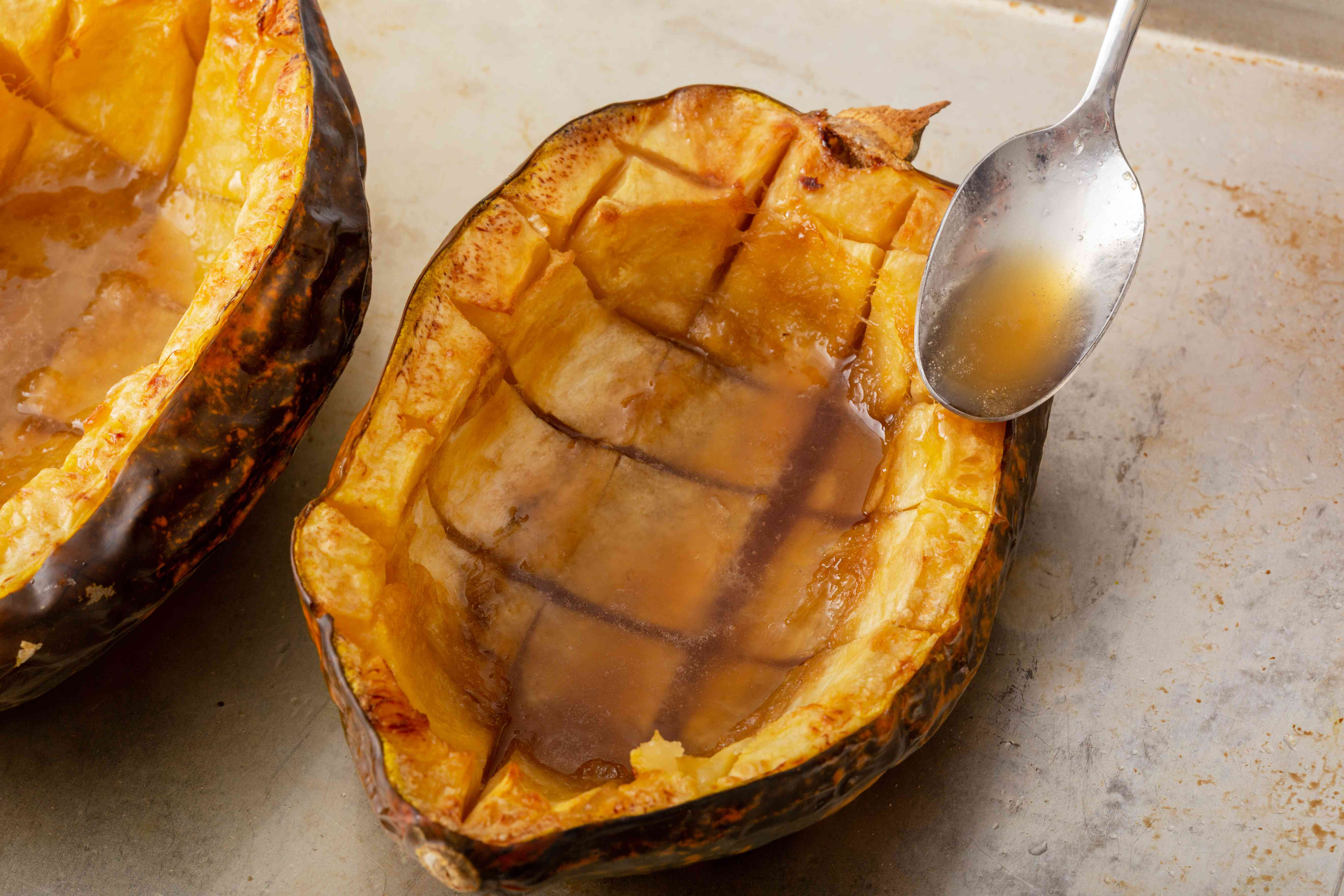Baked acorn squash with sauce spooned overtop.