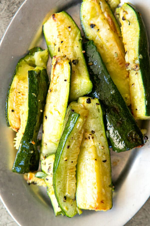 Roasted Zucchini with Garlic on a serving platter sprinkled with black pepper