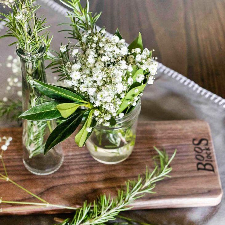 babys breath in mason jar on wood cutting board