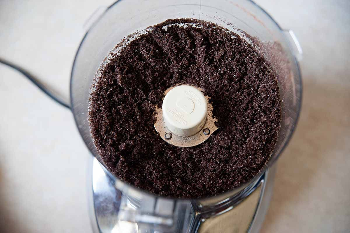 A shot of chocolate graham crackers ground up in a food processor with melted butter poured over the top to make the crust for a homemade chocolate cheesecake.
