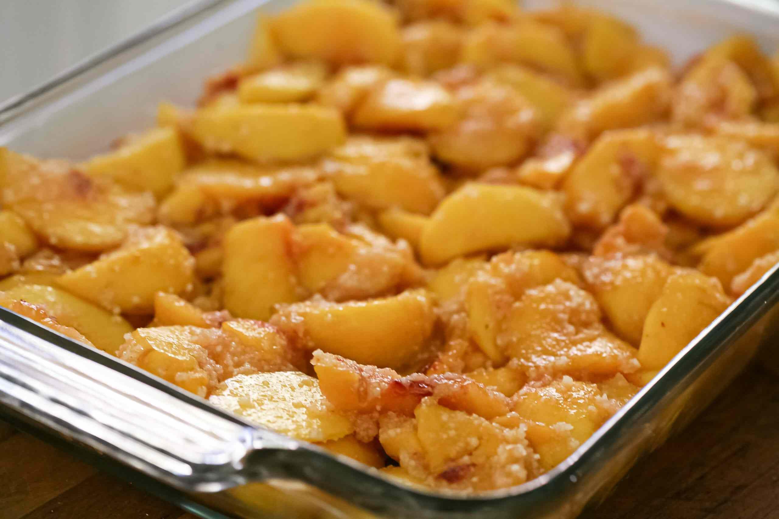 All the peaches for homemade peach cobbler in a baking dish