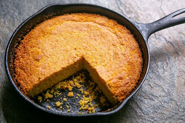 Cornbread recipe baked in a cast iron skillet with a large slice removed.