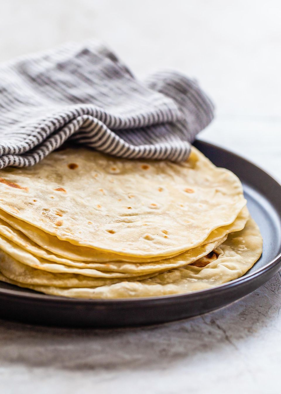 A close up of a stack of homemade flour tortillas on a platter covered by a striped towel.