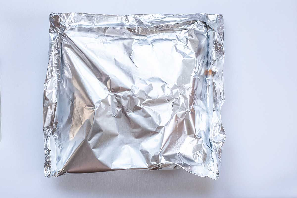 White background with a top view of a sheet of foil on a baking sheet.