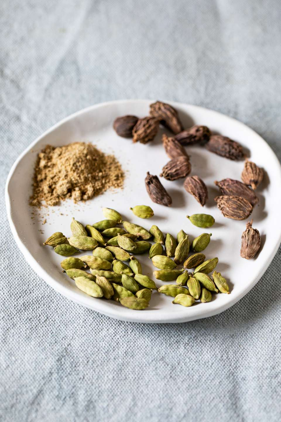 Ground cardamom and green and brown cardamom pods on a white plate