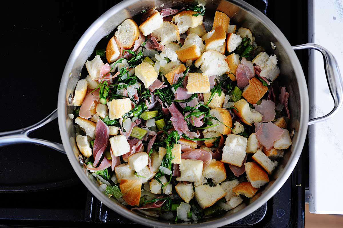 A high-sided skillet has chopped bread, prosciutto, herbs and asparagus mixed inside for a breakfast strata.