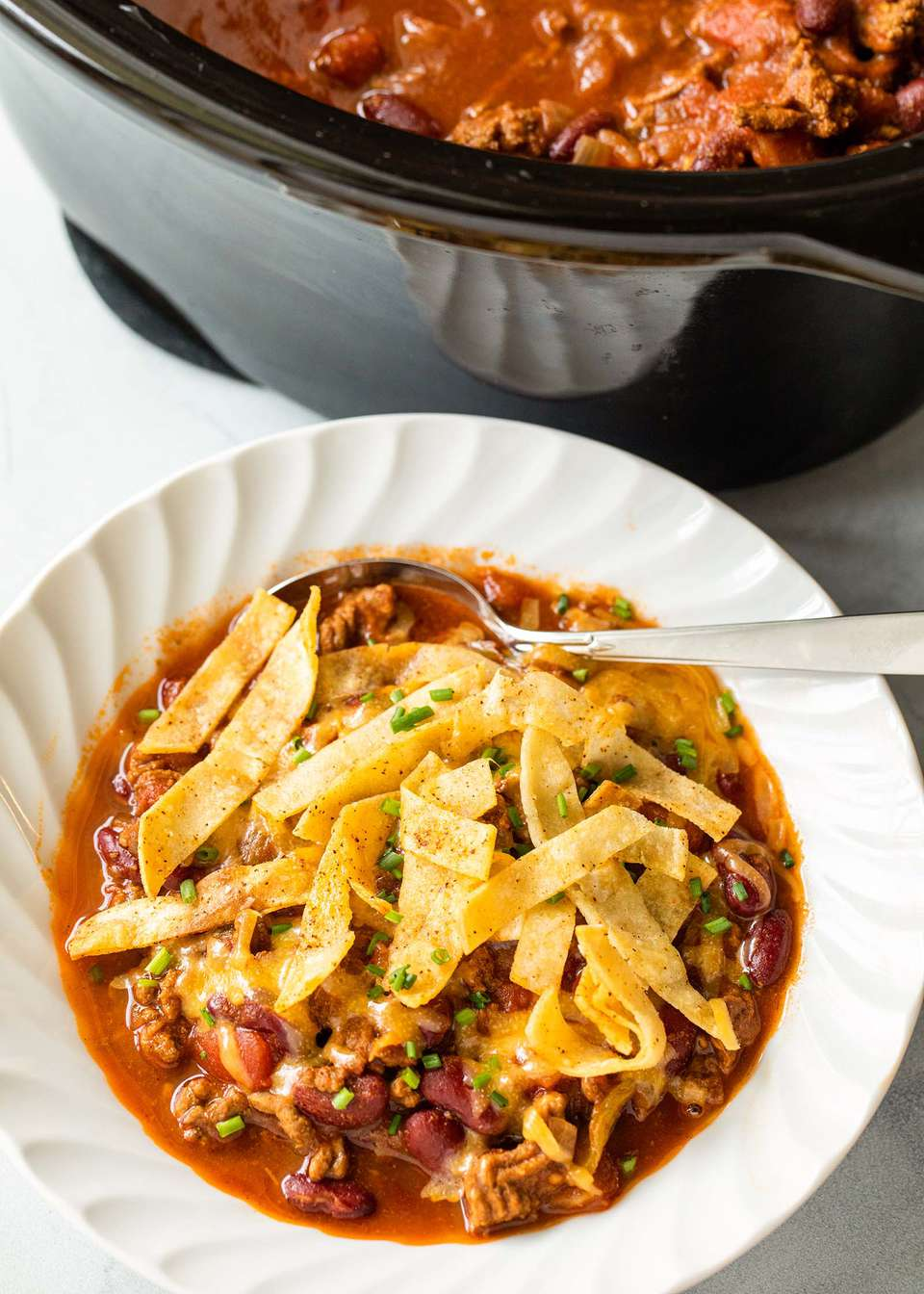 A bowl of Tailgate Beef Chili Recipe topped with fried tortilla strips with a crock pot set above it.
