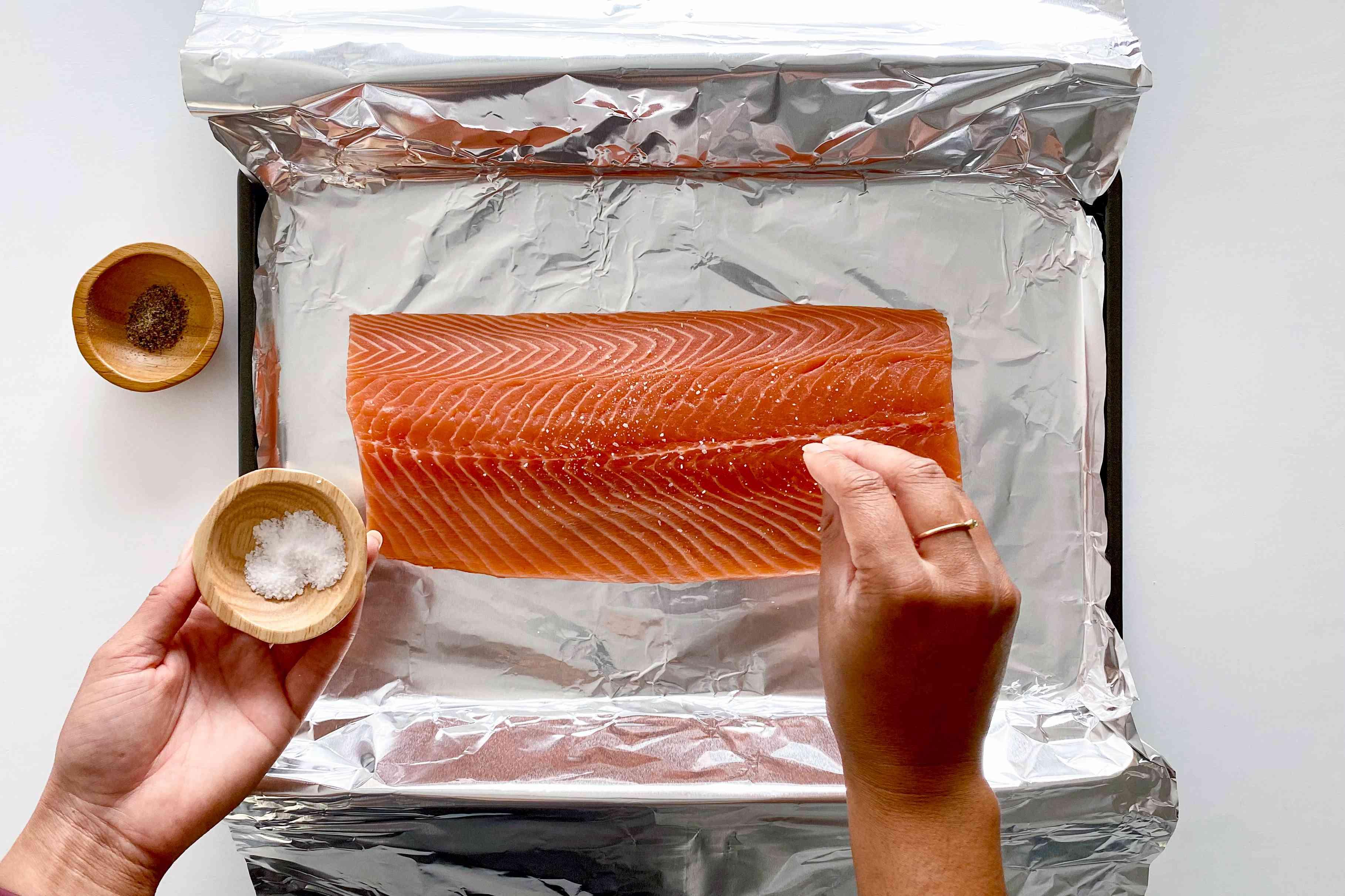 Seasoning salmon on a foil lined baking sheet to make Garlic Butter Baked Salmon.