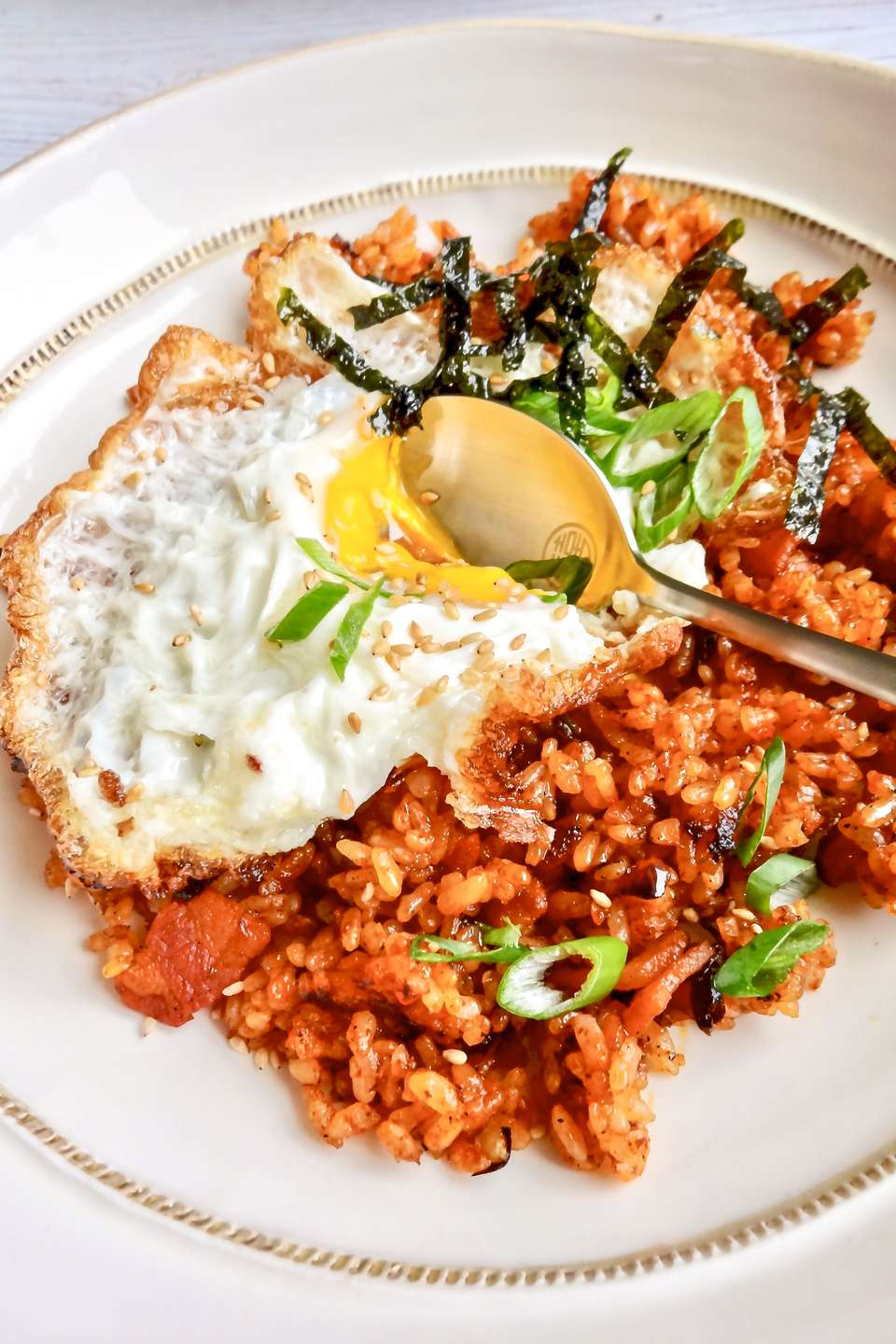Kimchi fried rice with a fried egg served in a bowl in white bowl.