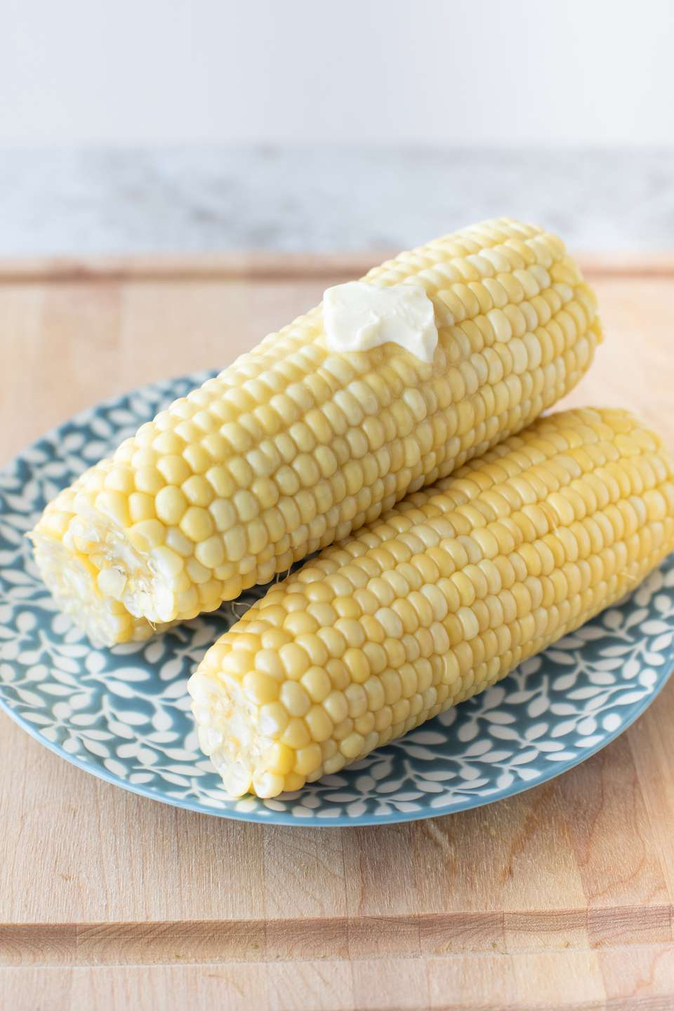 Cooked corn on the cob ears with a pat of butter on a blue flower plate