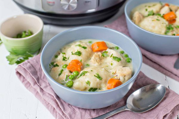 A blue bowl on a pink cloth filled with chicken and dumplings with an instant pot in the background.