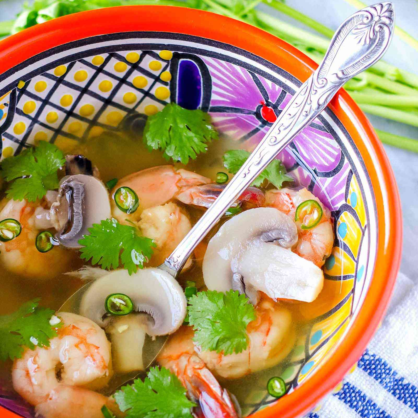 Vertical view of brightly patterned bowl with a silver spoon inside. Tom yum soup with shrimp, cilantro and mushrooms in a light broth are in the bowl. Above the bowl are stems of cilantro and below the bowl is a blue striped linen.
