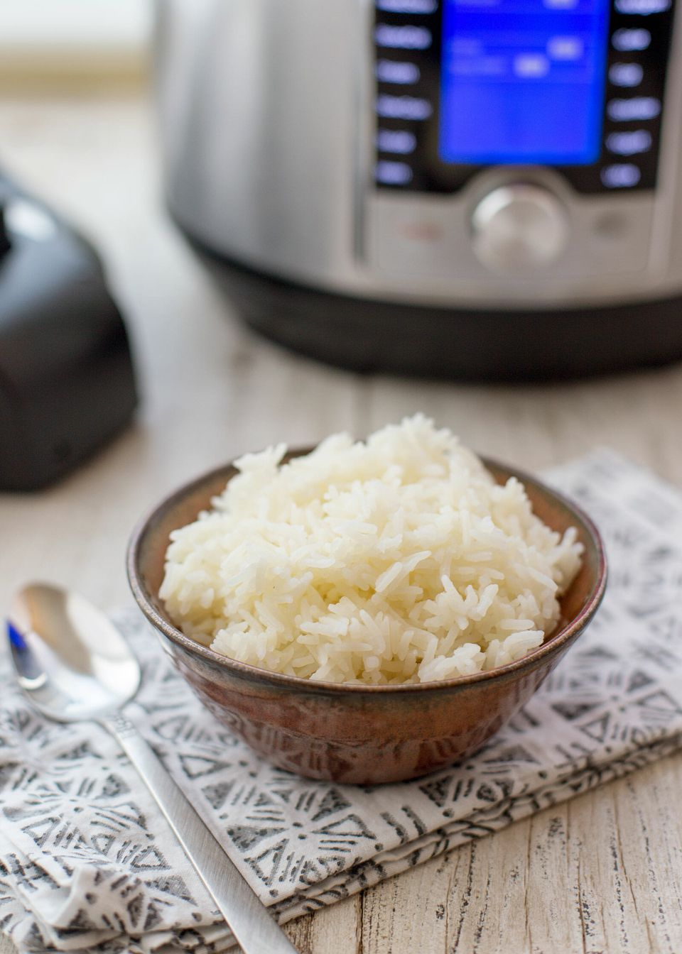 A bowl of instant pot rice with the instant pot in the background