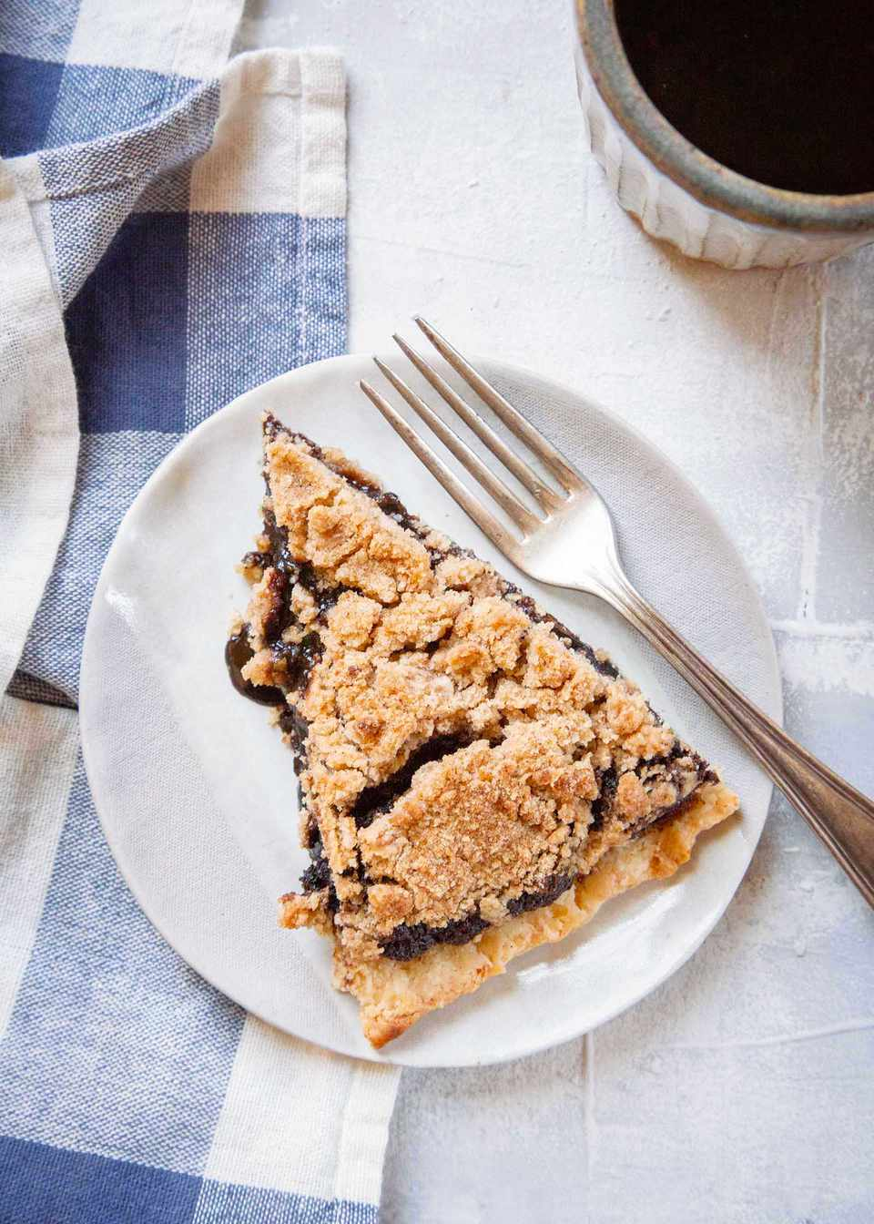 Shoo-fly pie on a white plate with a fork next to it.