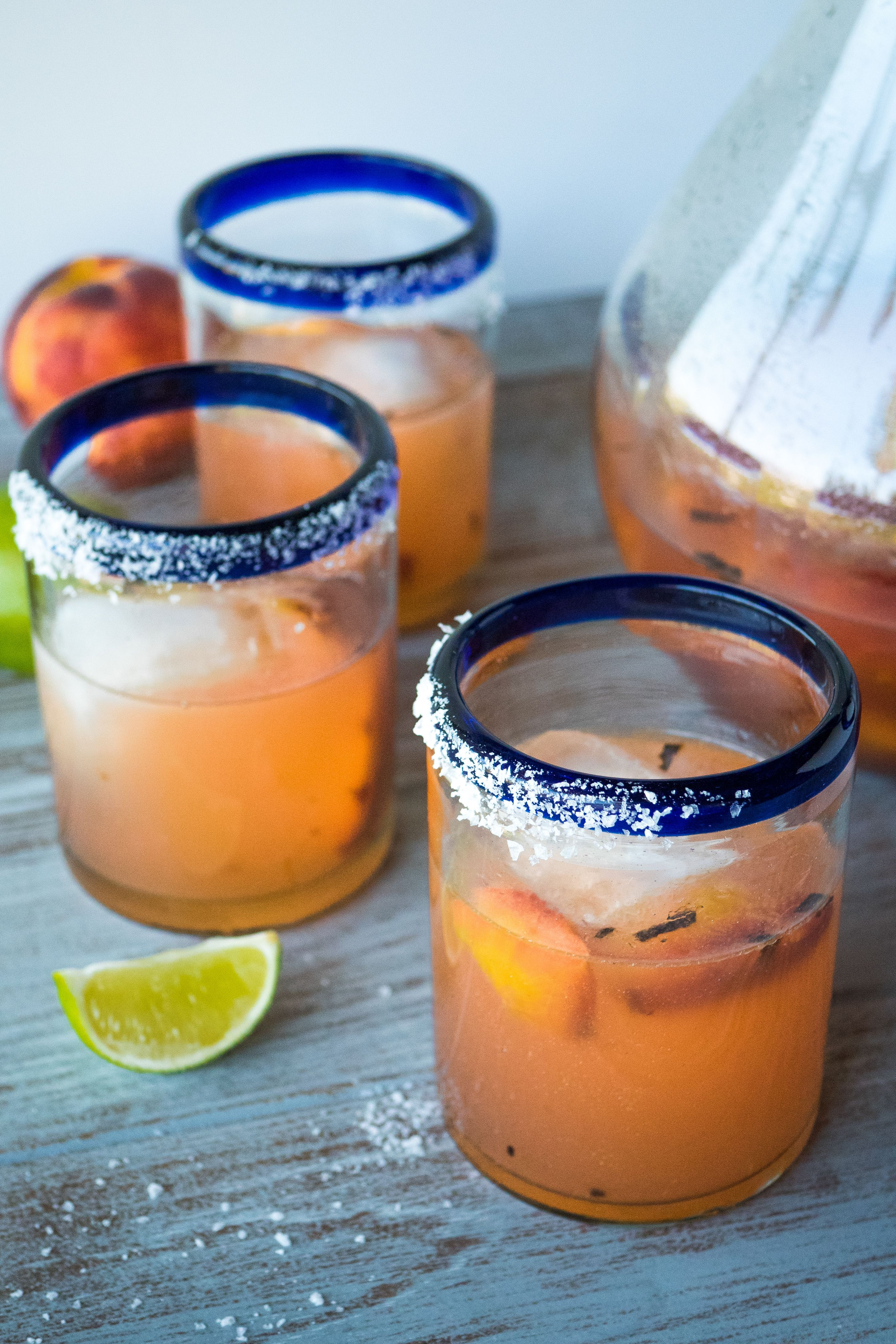 Three grilled peach pitcher margaritas on a table with limes and a pitcher.