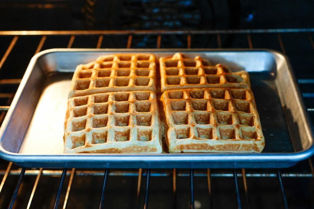 A small baking sheet in the oven with waffles inside.