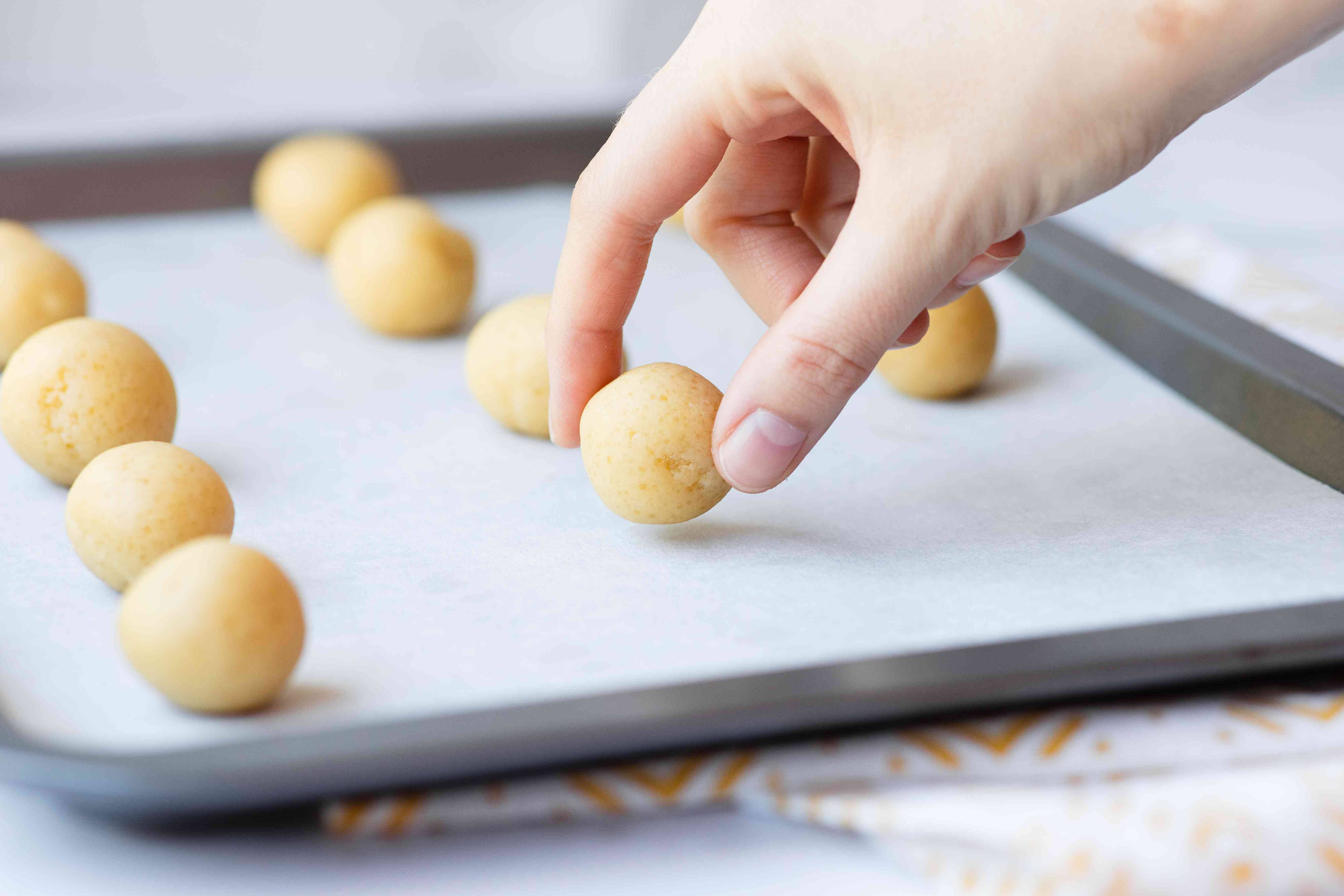 Balls of dough set on a parchment covered baking sheet to make a Chinese almond cookie recipe.
