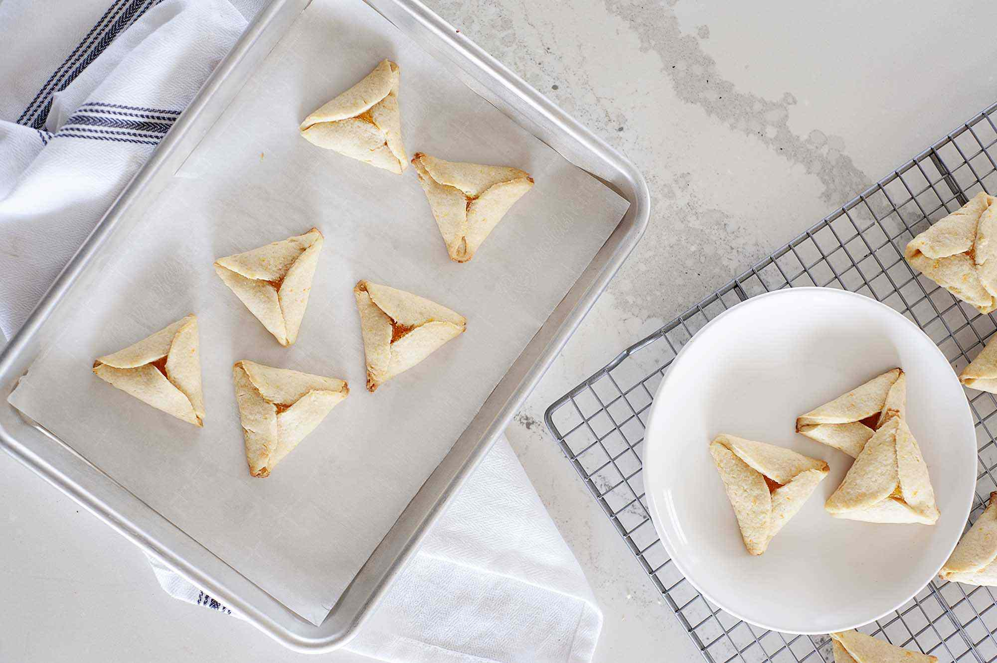 Apricot Hamantaschen on a white plate with a baking sheet set at a diagonal and more of the buttery Apricot Hamantaschen on a cooling rack.