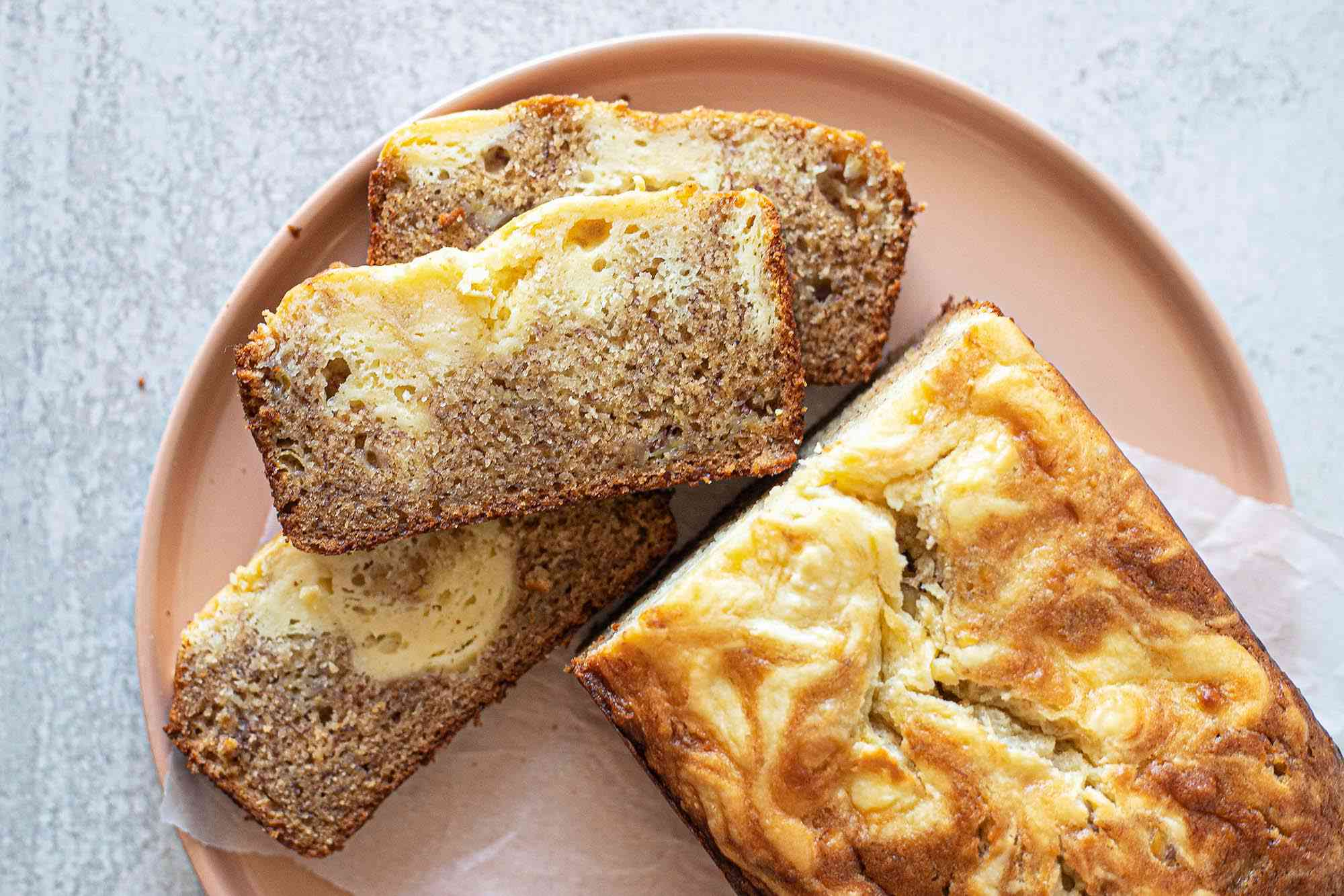 Overhead view of a loaf of banana bread with cream cheese on a plate. Three slices are laying in front of the loaf.