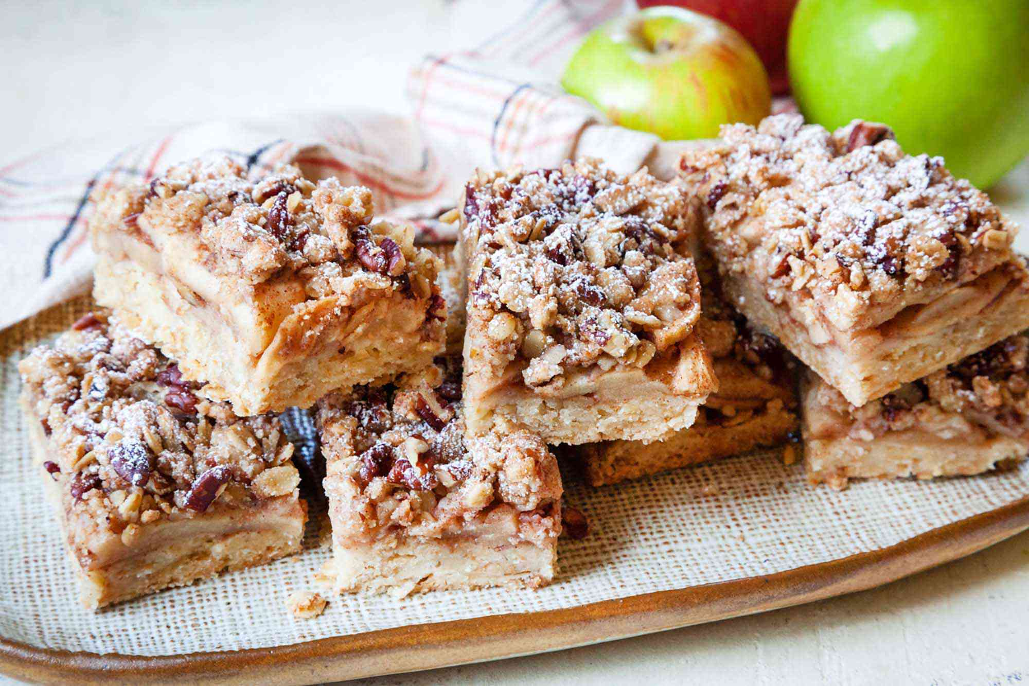 Apple pie bars with pecan oat crumb topping stacked on a platter with apples behind them.
