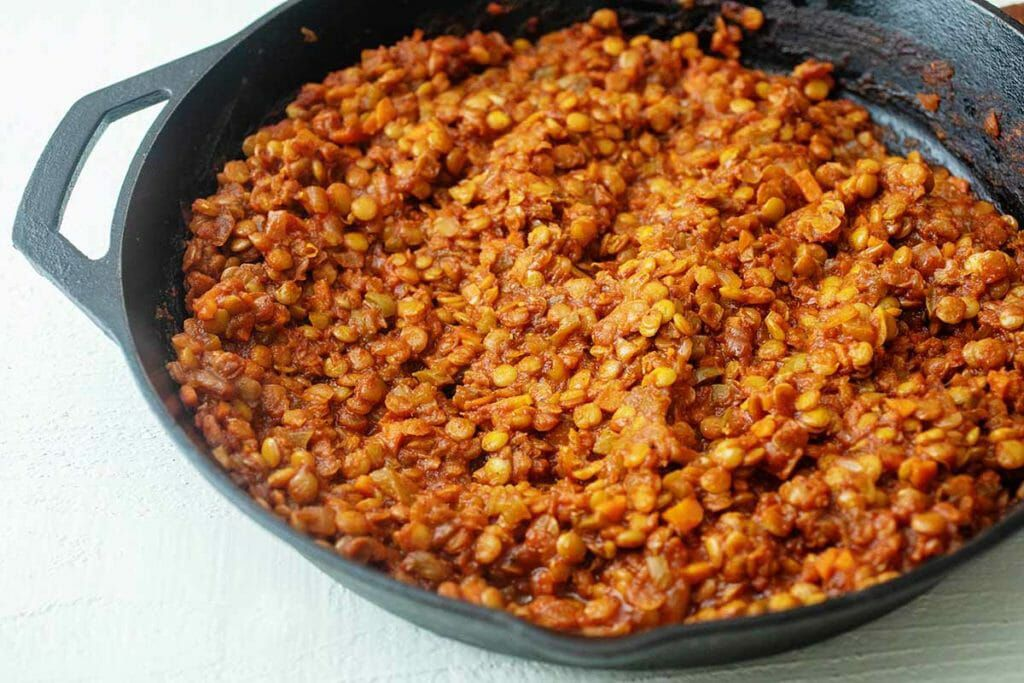 Cook lentils and tomatoes in a cast iron skillet for vegan vegetarian sloppy joes