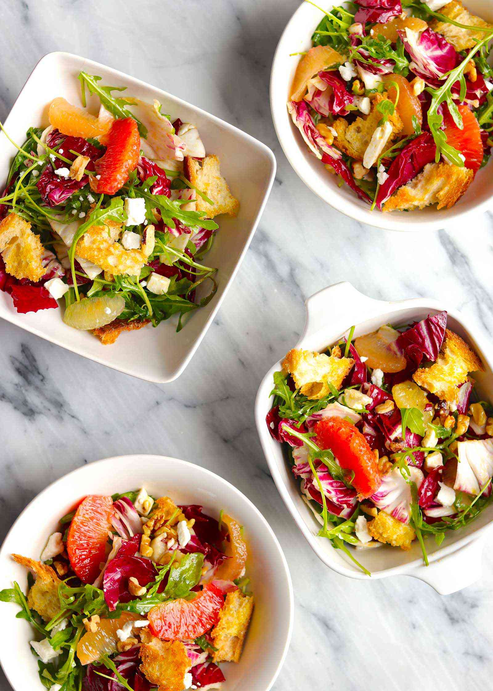Overhead view of four white bowls with winter salad inside. Arugula, radicchio, supremed citrus, croutons and crumbled feta are visible in each bowl.