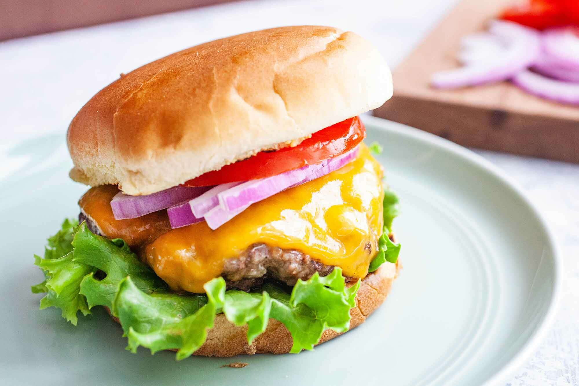 Grilled burger on a plate with cheese, onions, and tomatoes