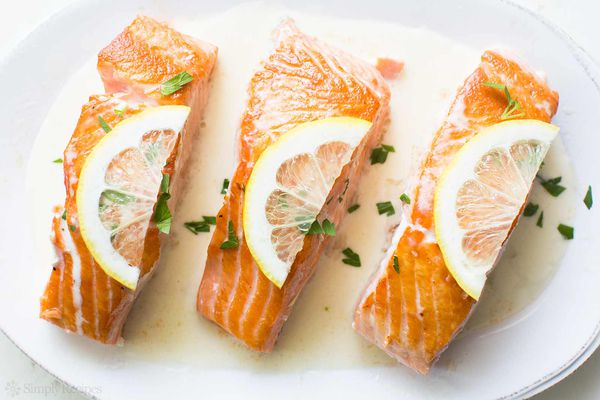 three cooked salmon with lemon on a white plate