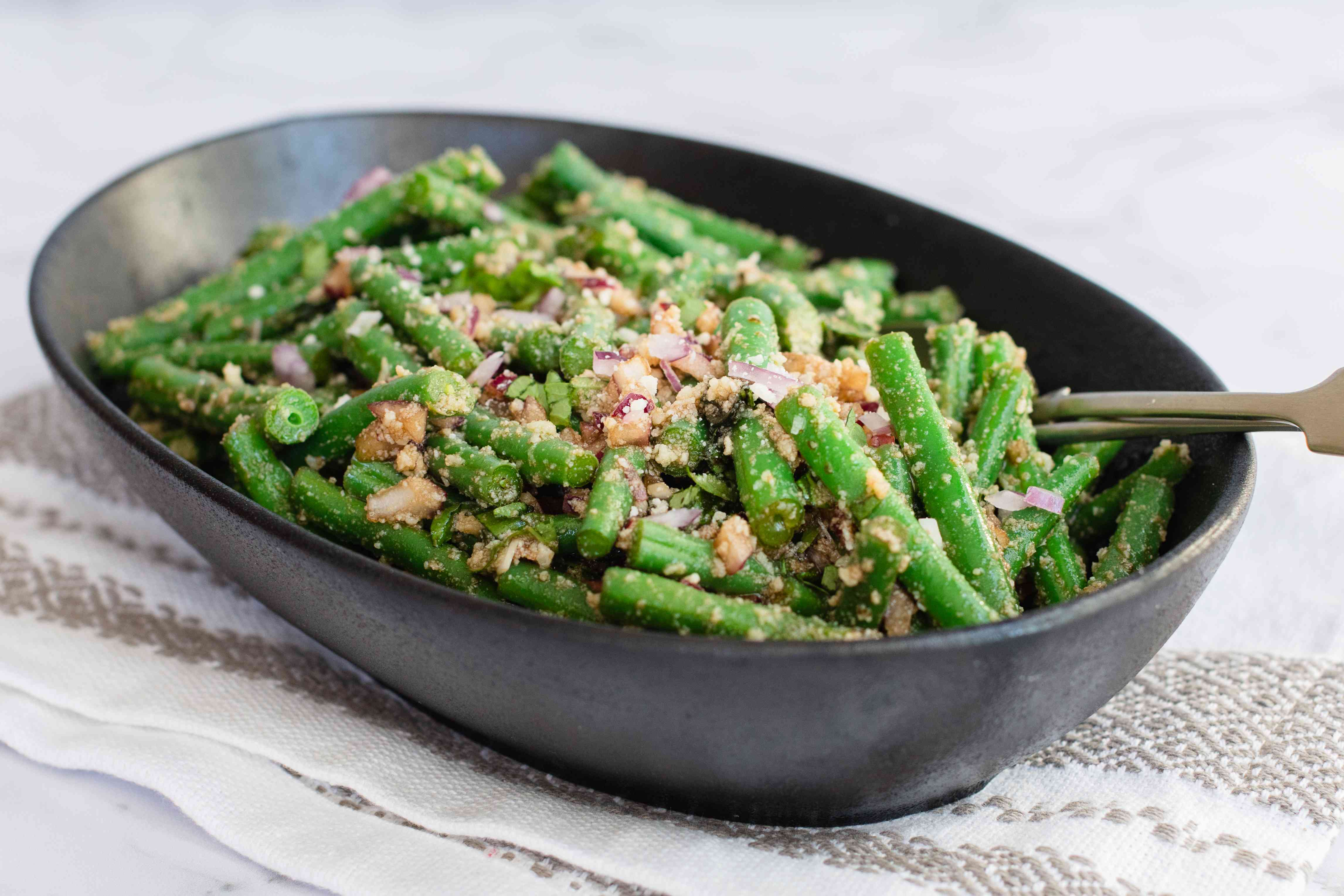 Side view of green bean salad in a serving bowl.