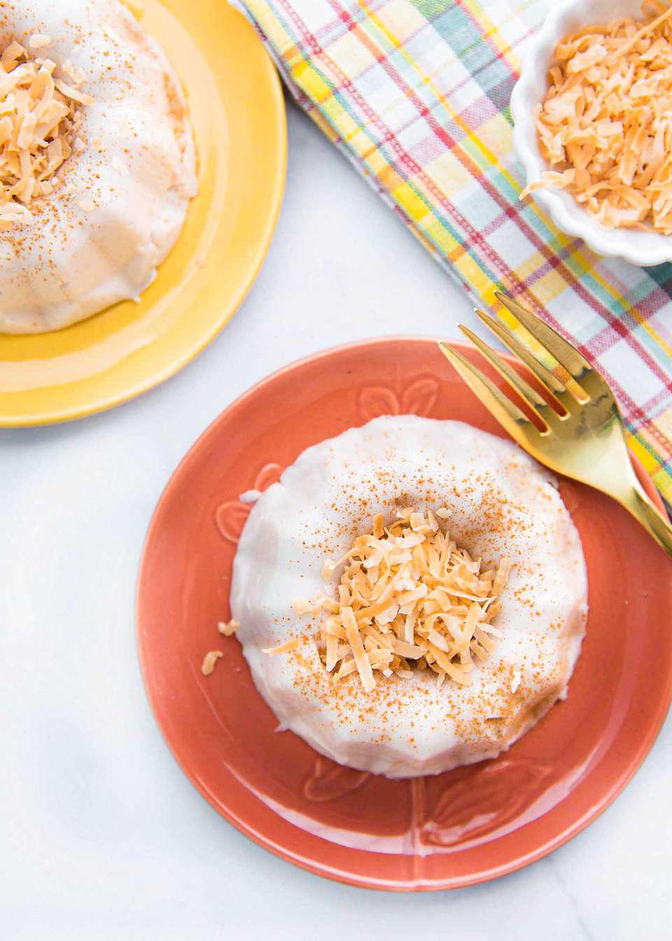 Vertical photo of two plates with coconut pudding with toasted, shredded coconut mounded inside the bundt shape. The coconut pudding is coated in ground cinnamon. The lower plate is coral and a gold fork is to the left of it, the plate in the upper left is light yellow. A small container of toasted shredded coconut is to the right of the coral plate. A striped dish cloth is underneath the coconut.