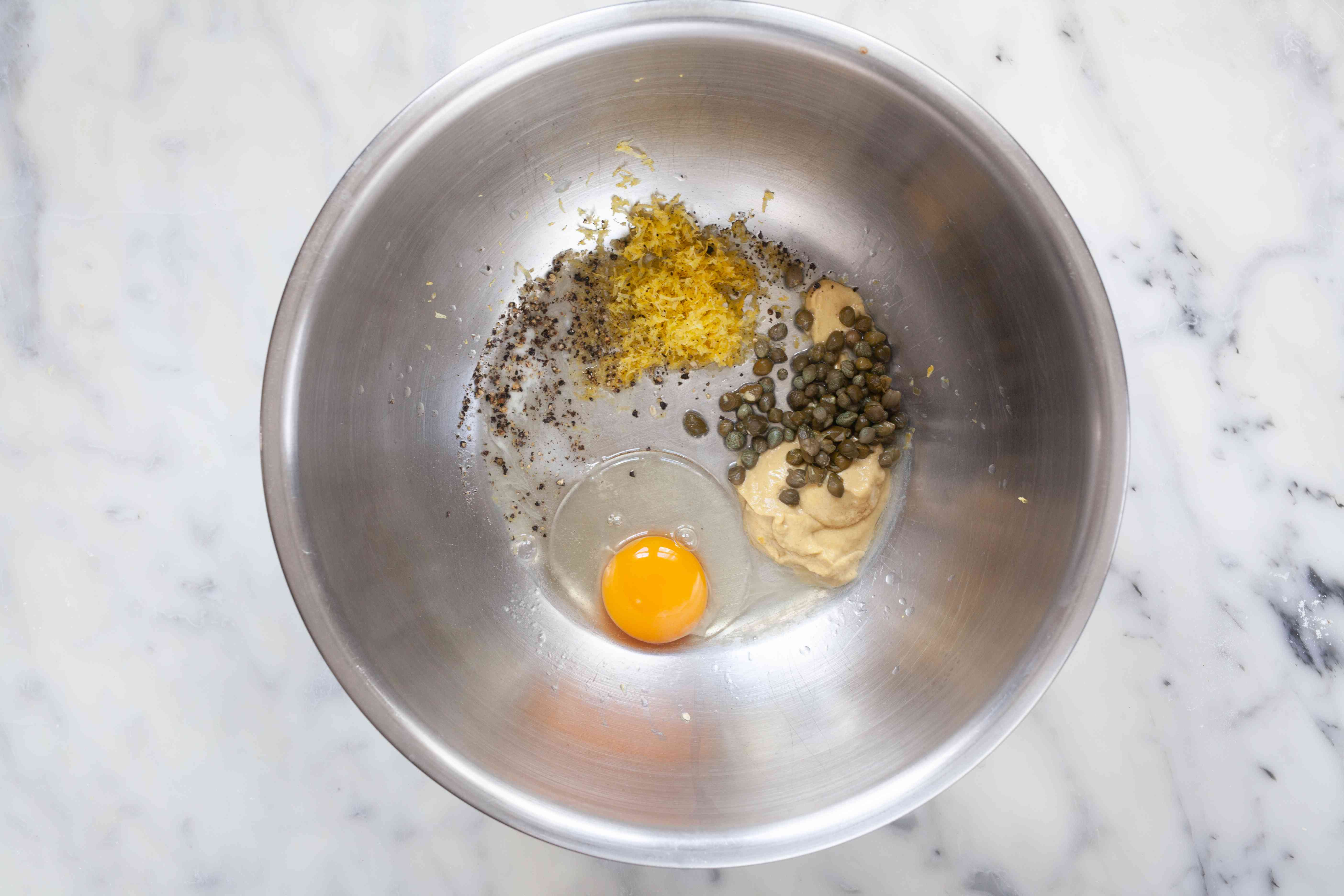 Egg and spices in a metal bowl to make a salmon burger recipe.