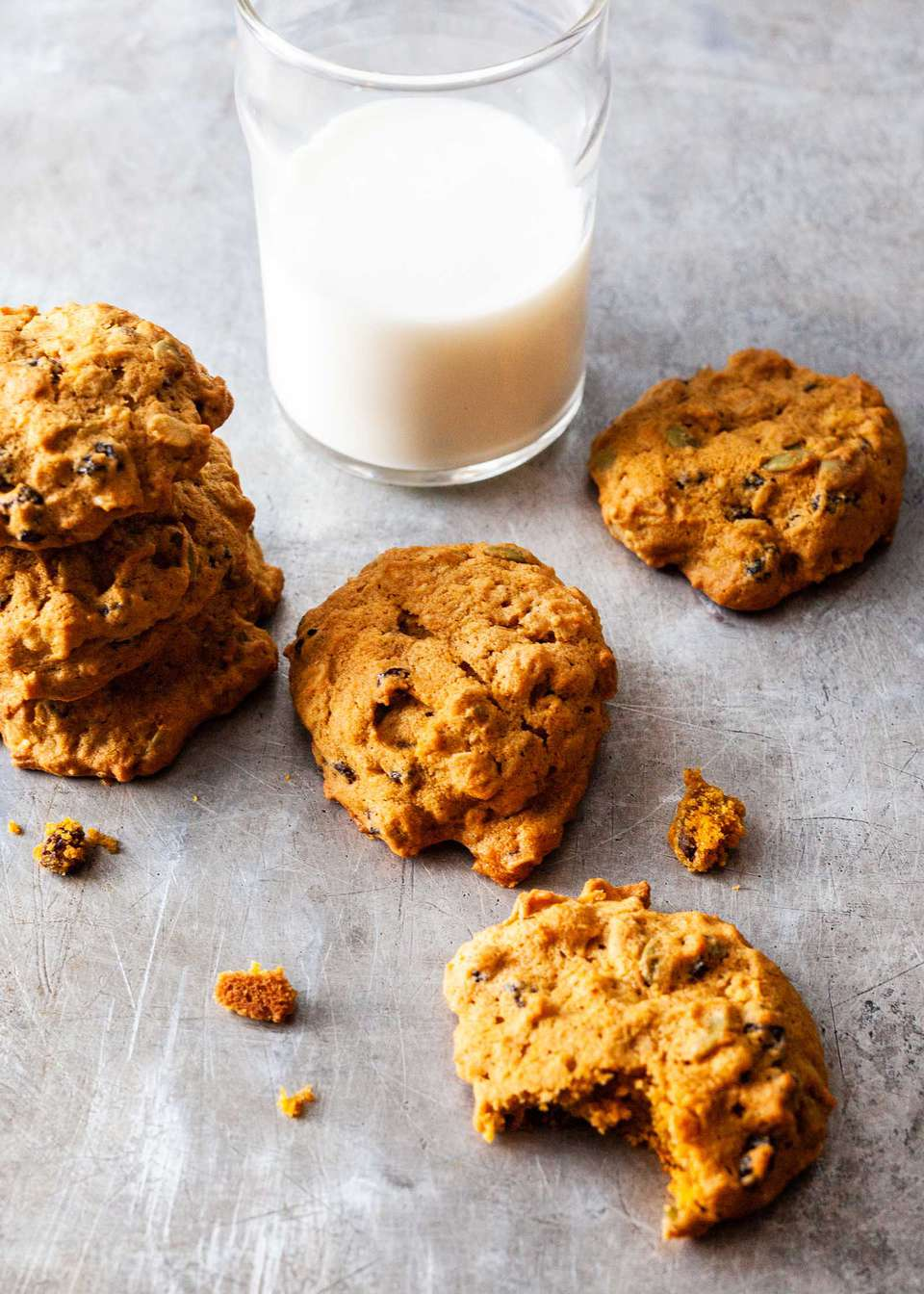 Pumpkin spice cookies on a counter with a glass of milk.